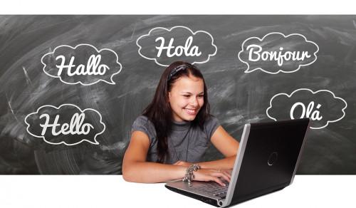 Dziewczynka z komputerem, laptopem. W tle tablica z napisem dzień dobry w obcych językach
