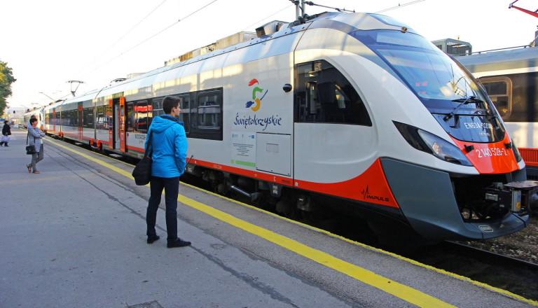 Mężczyzna w niebieskiej kurtce stoi na peronie obok pociągu