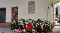 Rocznica Pogromu żydowskiego W Kielcach . Kamienica przy ul Planty 7 w Kielcach, złożone wiązanki kwiatów przed tablicą upamiętniającą pomordowanych