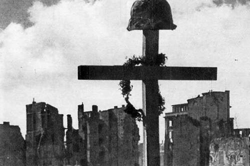 Krzyż wbity w ziemię, a na nim powstańczy hełm. Zdjęcie archiwalne z Powstania Warszawskiego.