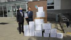 Jacek Sambór i Andrzej Bętkowski stoją przed budynkiem Urzędu Marszałkowskiego, obok nich leżą na ziemi rzeczy, które otrzymała placówka w Kazimierzy Wielkiej.