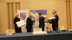 Renata Janik, Andrzej Bętkowski oraz Zbigniew Koniusz wręczają Jackowi Sambórowi podpisaną umowę i symbolicznie dwa laptopy.