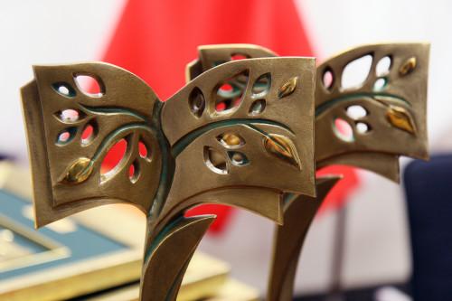 Statuetki Świętokrzyskiej Nagrody Kultury. W rozmytym tle biało czerwona