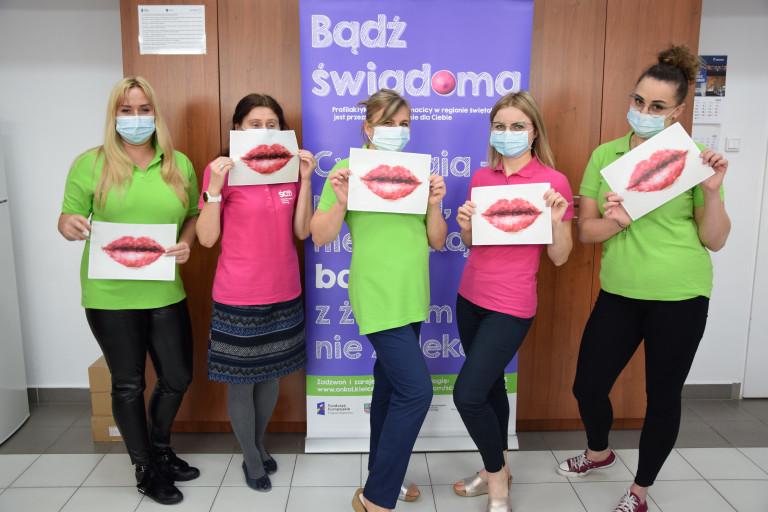 5 Kobiet Stojących Przed Banerem Treklamującym Akcję Profilaktyczną Trzymających W Dłoniach Kartki Z Grafikami Przedstawiającymi Usta.