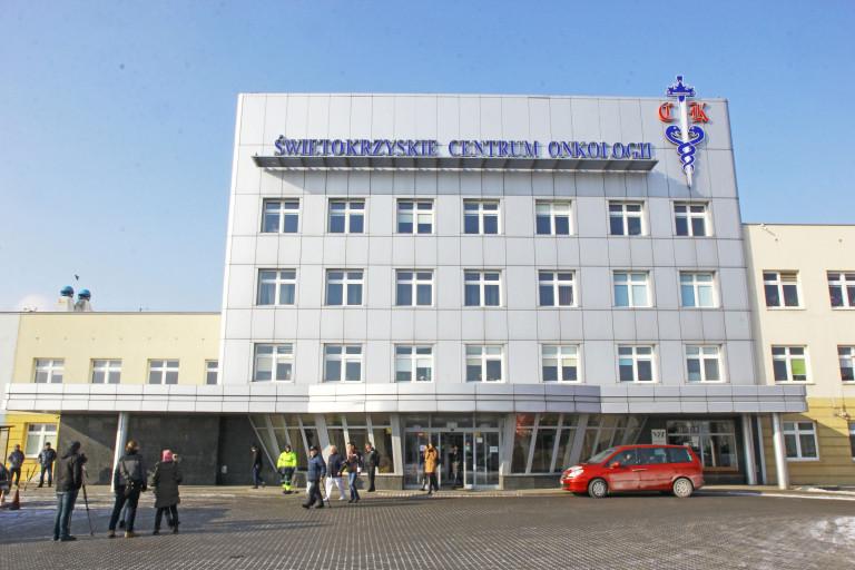 Główne Wejście do Budynku, Świętokrzyskiego Centrum Onkologii Przy Ulicy Artwińskiego W Kielcach. Z budynku wychodzą pacjenci. Przed wejściem zaparkowany czerwony samochód typu van
