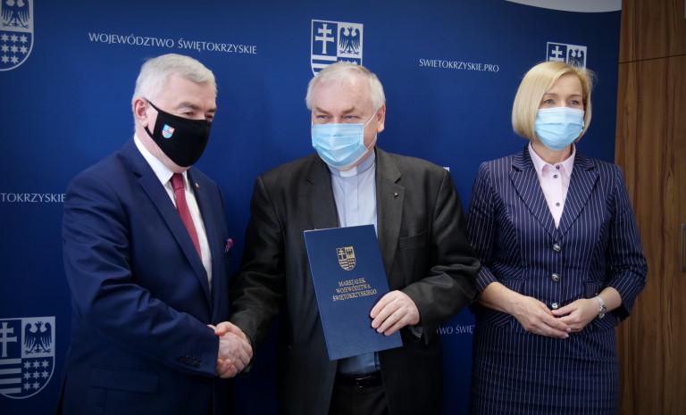 Wręczenie umowy księdzu Stanisławowi Słowikowi przez Marszałka Andrzeja Bętkowskiego i wicemarszałek Renatę Janik