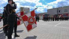 Poczet Sztandarowy Złożony Z Trzech Strażaków Trzyma Opuszczoną Flagę.