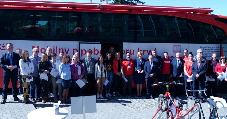 Zbiorowe Zdjęcie Uczestników Oddawania Krwi Stojących Przed Autokarem Poboru Krwi Na Parkingu Przed Urzędem Marszałkowskim