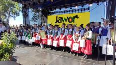 Rozstrzygnięcie konkursu Jawor. Na scenie z dyplomami i nagrodami w rękach. młode dziewczynki, kobiety i mężczyźni w strojach ludowych