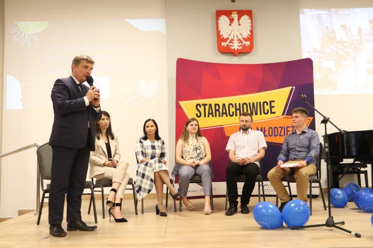 Andrzej Pruś Przemawia Do Mikrofonu Stojąc. W Tle Kilka Osób Siedzi Na Krzesłach