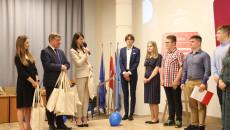 Andrzej Pruś Stoi Z Torebkami W Ręku W Których Są Nagrody Dla Uczestników, Obok Niego Dwie Kobiety I Kilku Młodych Ludzi