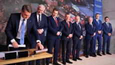 Grupa Ośmiu Mężczyzn, Uczestników Uroczystości Stoi Na Scenie, Jacek Semaniak Sięga Dłonią Po Tubę W Której Znajduje Się Akt Erekcyjny