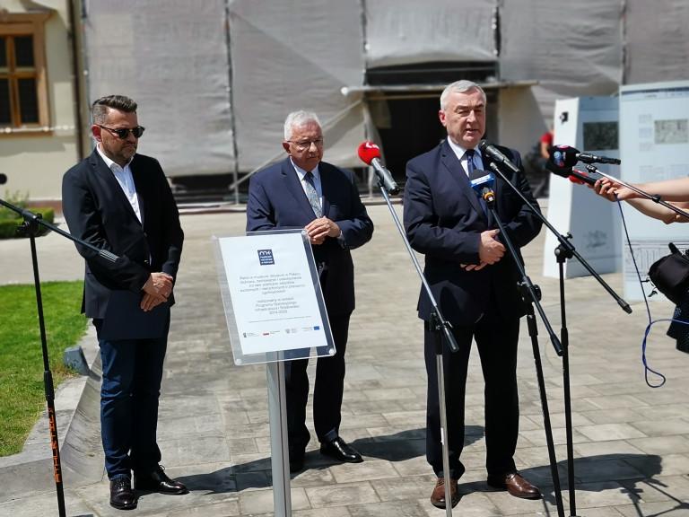 Trzech mężczyzn, w garniturach, stoi przed mikrofonami. Do dziennikarzy przemawia, Andrzej Bętkowski, marszałek województwa świętokrzyskiego