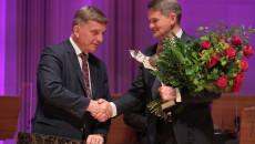Przewodniczący Sejmiku Województwa Andrzej Pruś gratuluje profesorowi Jackowi Semaniakowi, który trzyma statuetkę Świętokrzyskiej Victorii oraz bukiet róż
