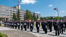 Kilkudziesięciu Strażaków Stoi W Równych Rzędach Przed Urzędem Wojewódzkim Trzymając W Rękach Akty Zakupu Samochodów I Promesy Na Zakup Samochodów Strażackich