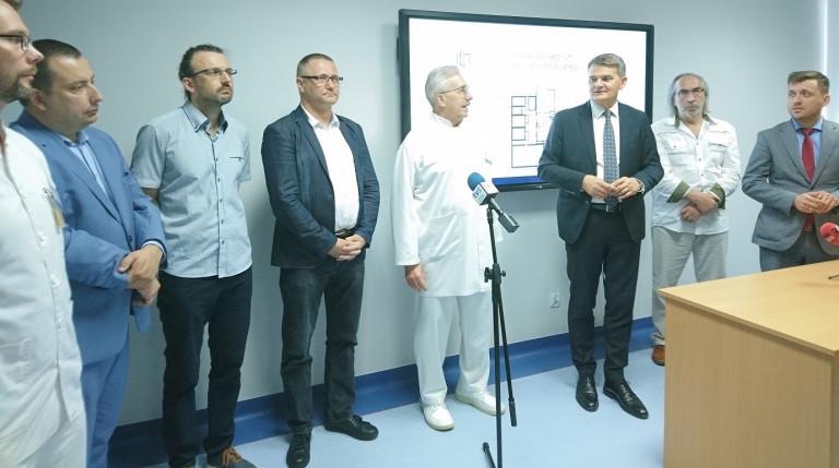 Mężczyźni w garniturach, lekarze w białych fartuchach, stoją przed mikrofonami. Za nimi, na ścianie telewizor. Napis samodzielne laboratorium promieniowania jonizującego
