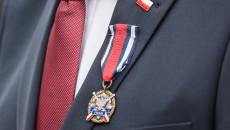 Zdjęcie zbliżenie, na Medal w butonierce marynarki marszałka Andrzeja Bętkowskiego. Nad medalem flaga Polski