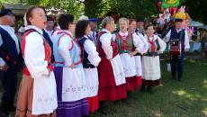 Występy ludowe. Kobiety ubrane w kolorowe stroje ludowe, śpiewają w towarzystwie grających na instrumentach muzycznych, mężczyzn
