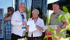 Andrzej Bętkowski wręcza uczestniczce, starszej gospodyni w stroju ludowym, dyplom. Obok stoi mężczyzna trzymający w rękach pudło z nagrodą