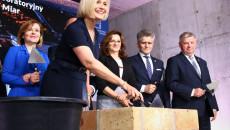 Renata Janik Z Kielnią W Ręku, W Tle Kilku Uczestników Uroczystości.