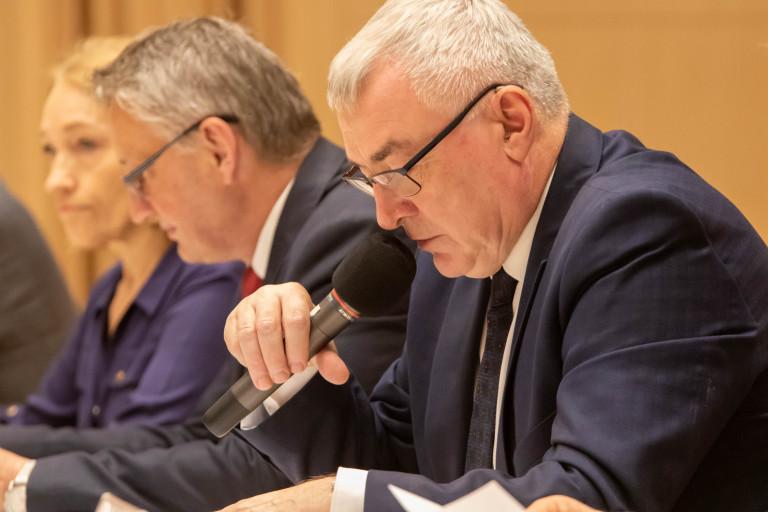Siedzący Za Stołem Andrzej Bętkowski Mówi Do Mikrofonu, W Tle Wojewoda Zbigniew Koniusz.