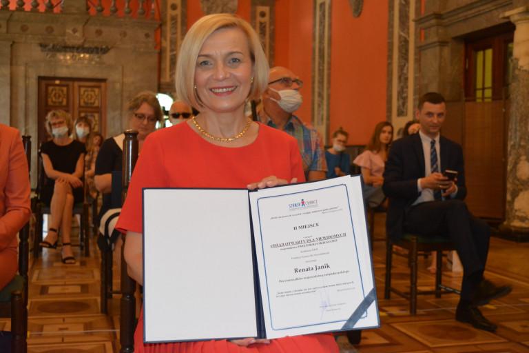 Pamiątkowa fotografia. Wicemarszałek Renata Janik Prezentuje Dyplom regionalnego konkursu, Idol, Fundacji Szansa dla Niewidomych
