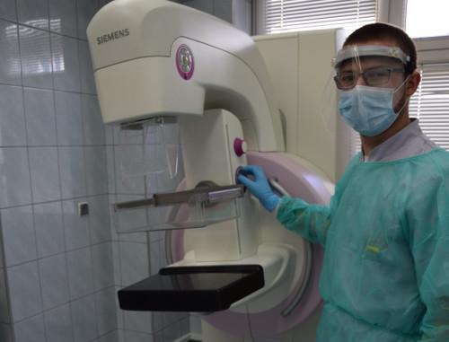 Lekarz ubrany w odzież ochronną stoi obok aparatury do mammografii