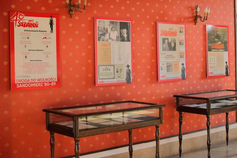 Na czerwonej ścianie, cztery duże reprodukcje ze znakiem Solidarność, czwarty czerwca! Archiwalne zdjęcia, dokumenty, nekrolog. Fragment Wystawy. Droga Do Wolności Sandomierz 80 89