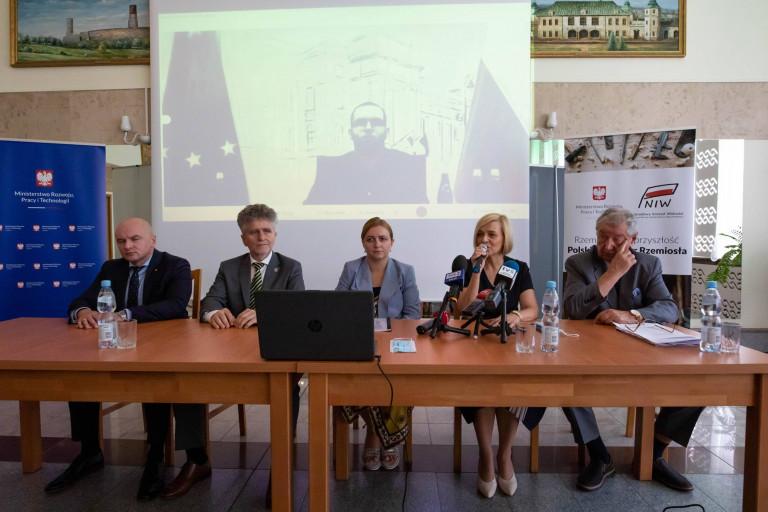 Za stołem siedzi kilka osób. Wśród nich przemawiająca z mikrofonem wicemarszałek Renata Janik