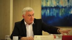 Obrady komisji. Siedząc za stołem marszałek Andrzej Bętkowski sięga po dokumenty