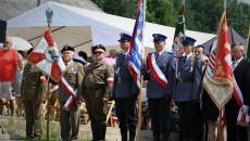 Grupa ludzi w mundurach policyjnych oraz kombatantów stoi ze sztandarami, między innymi sztandar województwa świętokrzyskiego