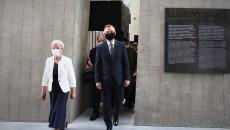 Andrzej Duda i Marianna Wikło wchodzą do budynku Mauzoleum. Na ścianie tablica z informacją, duży napis, ludobójstwo, w języku angielskim genocide