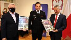 Marszałek województwa świętokrzyskiego Andrzej Bętkowski i wojewoda Zbigniew Koniusz gratulują strażakowi. Trzymają w rękach pamiątkowe zdjęcia z zawodów