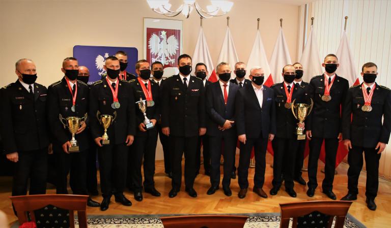 Grupa mężczyzn w mundurach pozuje do pamiątkowej fotografii. Drużyna sportowa Państwowej Straży Pożarnej z województwa świętokrzyskiego ze zdobytymi pucharami i medalami