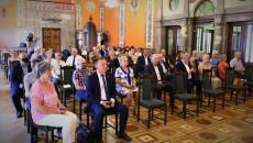 Uczestnicy spotkania siedzą na krzesłach w Sali Lustrzanej Wojewódzkiego Domu Kultury
