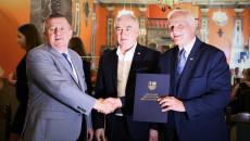 Marszałek Andrzej Bętkowski i członek Zarządu Województwa Marek Jońca gratulują mężczyźnie w jasnoniebieskim garniturze
