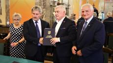 Marszałek Andrzej Bętkowski i członek Zarządu Województwa Marek Jońca gratulują mężczyźnie w ciemnym garniturze