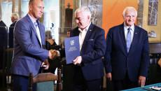 900a927Marszałek Andrzej Bętkowski i członek Zarządu Województwa Marek Jońca gratulują mężczyźnie w niebieskim garniturze
