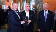 Marszałek Andrzej Bętkowski i członek Zarządu Województwa Marek Jońca gratulują mężczyźnie w granatowym garniturze i koszuli w biało-niebieską kratkę