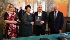 Marszałek Andrzej Bętkowski i członek Zarządu Województwa Marek Jońca gratulują kobiecie w czarnej sukience w białe groszki