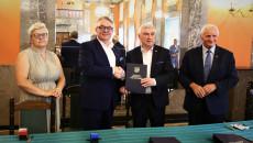 Marszałek Andrzej Bętkowski i członek Zarządu Województwa Marek Jońca gratulują mężczyźnie w ciemnym garniturze, białej koszuli i okularach