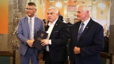 Marszałek Andrzej Bętkowski i członek Zarządu Województwa Marek Jońca gratulują mężczyźnie w niebieskim garniturze, białej koszuli i krawacie w biało-czarne paski