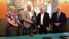 Marszałek Andrzej Bętkowski i członek Zarządu Województwa Marek Jońca gratulują mężczyźnie w beżowej marynarce i białej koszuli