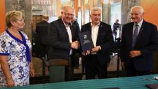 Marszałek Andrzej Bętkowski i członek Zarządu Województwa Marek Jońca gratulują uśmiechniętemu mężczyźnie w okularach, w ciemnym garniturze i białej koszuli