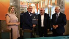 Marszałek Andrzej Bętkowski i członek Zarządu Województwa Marek Jońca gratulują mężczyźnie w ciemnym garniturze, białej koszuli i ciemnym krawacie