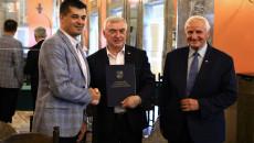 Marszałek Andrzej Bętkowski i członek Zarządu Województwa Marek Jońca gratulują mężczyźnie w marynarce w niebiesko-szarą kratę