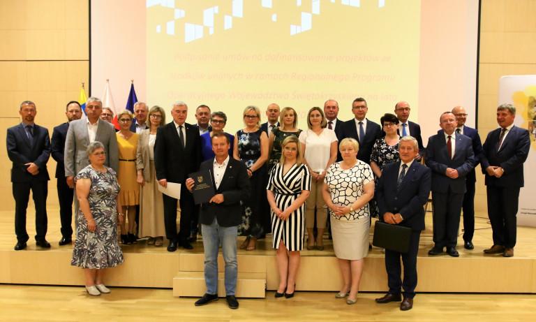 Szerokie zdjęcie, grupa osób stoi na podeście w sali kameralnej Filharmonii w Kielcach. Beneficjenci środków unijnych pozują do pamiątkowego zdjęcia