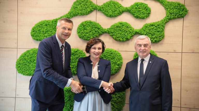 Bogdan Wenta, Justyna Lichosik, Andrzej Bętkowski pozują do pamiątkowej fotografii, ściskając swoje dłonie
