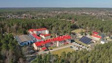 Szpital z lotu ptaka. W środku lasu, zespół budynków. Uwagę przykuwa czerwone zadaszenie oraz zespół paneli fotowoltaicznych o bardzo dużej powierzchni