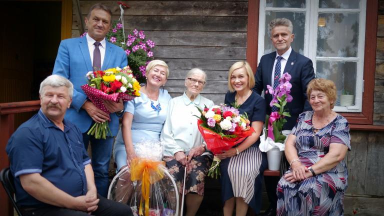 Pamiątkowa fotografia z Aleksandrą Sękowską, najstarszą mieszkanką gminy Łopuszno. Osoby zaproszone na jubileusz trzymają kwiaty